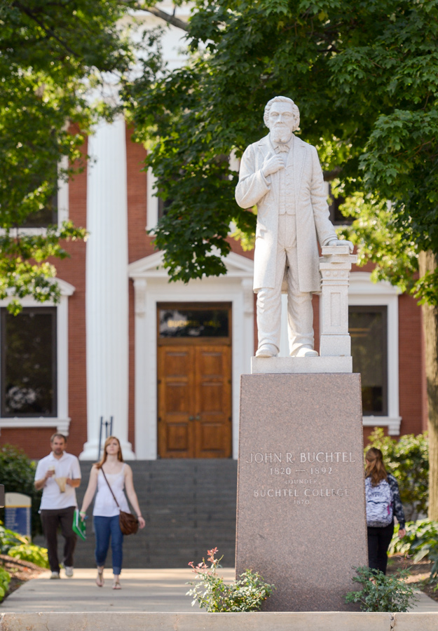 A student walks by a statue of University of Akron founder John Buchtel