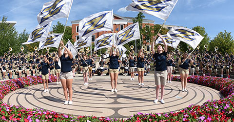 Marching band members twirl Akron flags during a performance