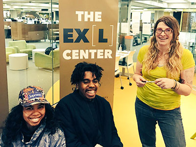 Three students together at the EXL Center located in Bierce Library.