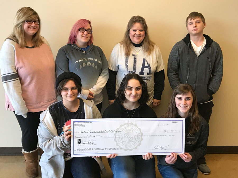 group posing with fundraising check