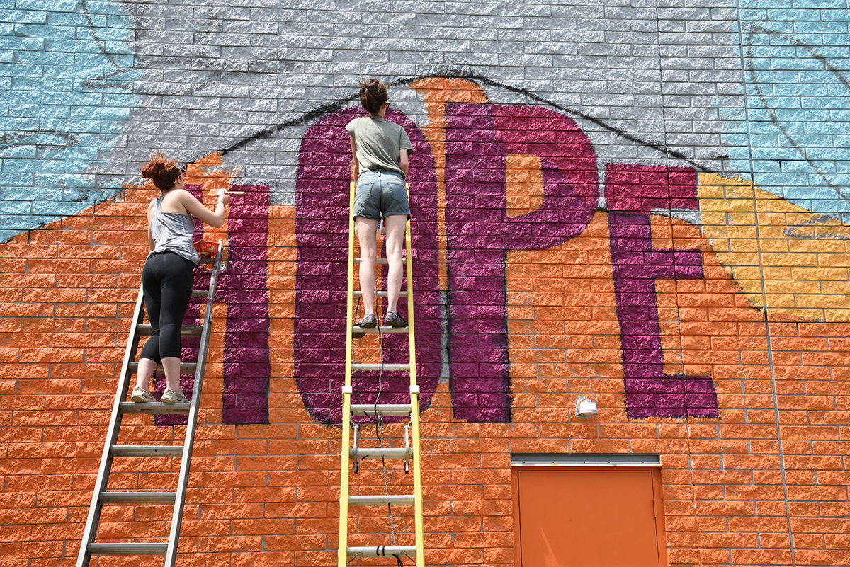 Members of the college's Art Bomb Brigade paint a mural on the side of a building in downtown Akron