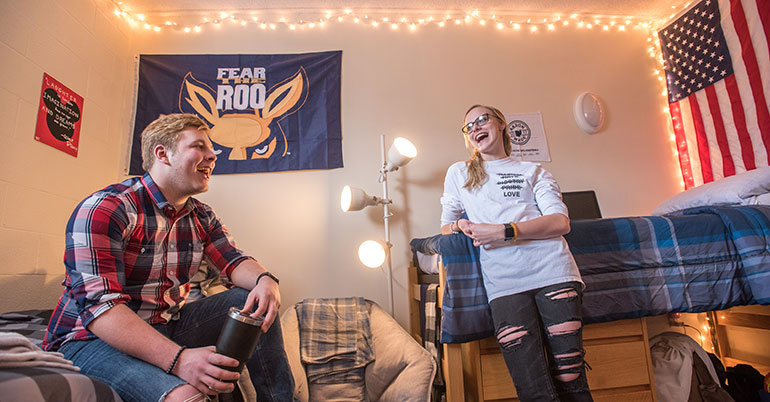 Two students talk in a residence hall at The University of Akron