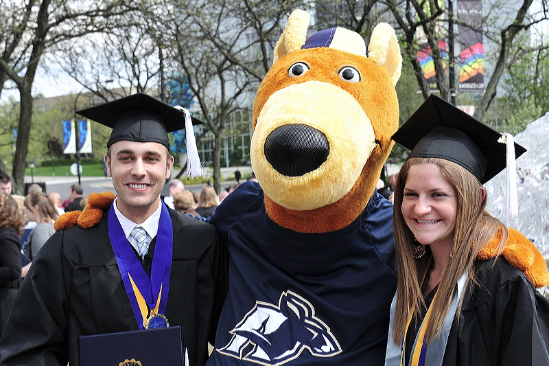Two UA students in graduation gowns, standing with the University of Akron mascot - Zippy